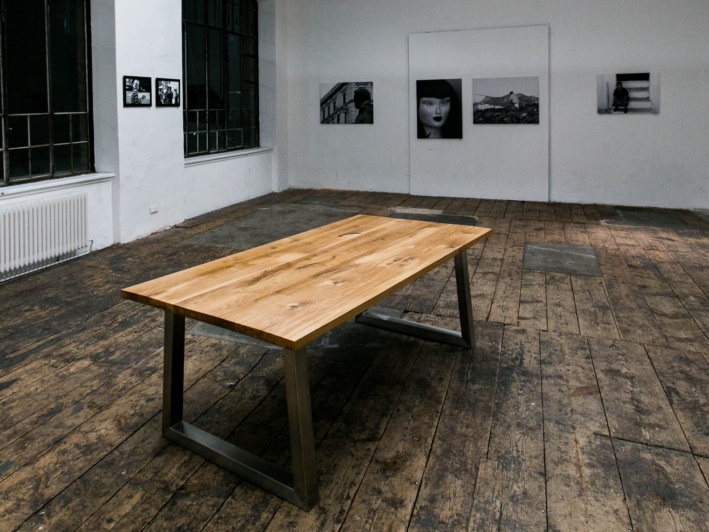 Ein Massivholztisch mit Eichenplatte auf einem Nirostagestell. Ausgestellt in einer Fabrikshalle im Zuge einer Fotovernissage.